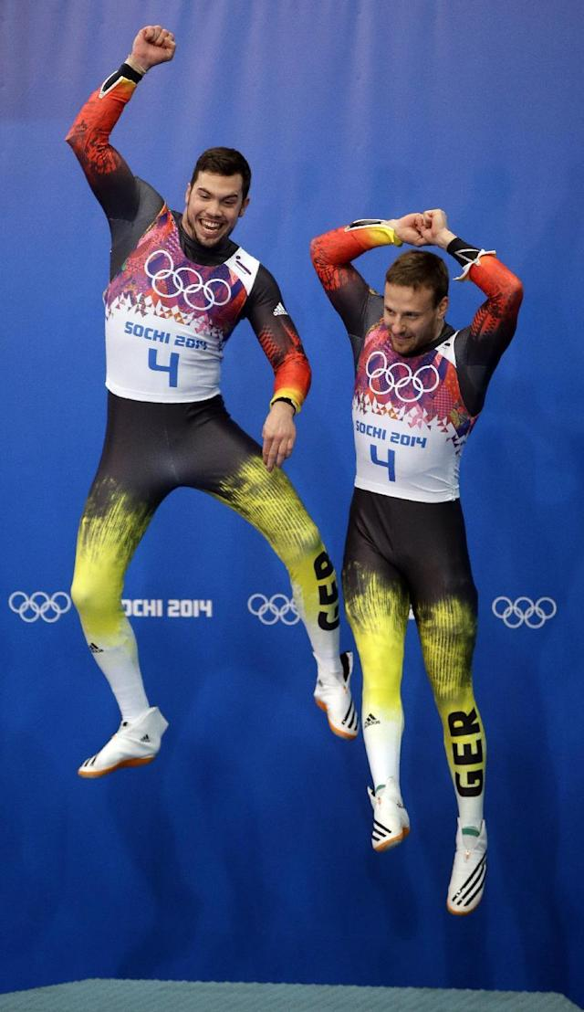 The doubles team of Tobias Wendl and Tobias Arlt from Germany jump onto the podium for the flower ceremony after they won the gold medal during the men's doubles luge at the 2014 Winter Olympics, Wednesday, Feb. 12, 2014, in Krasnaya Polyana, Russia. (AP Photo/Dita Alangkara)