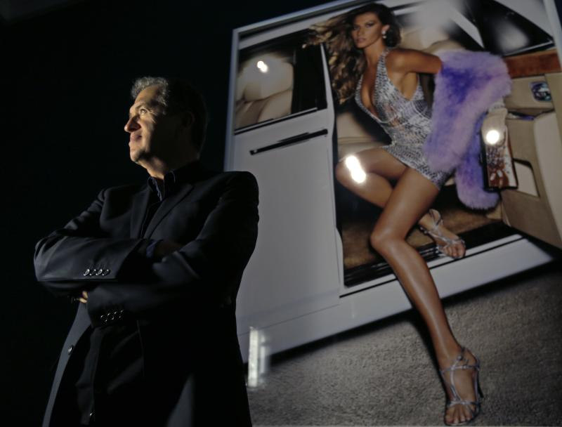 """Photographer Mario Testino poses for a portrait during the preview of his shows """"In Your Face"""" and """"British Royal Portraits"""" at the Museum of Fine Arts in Boston, Wednesday, Oct. 17, 2012. At right is his image of Gisele Bundchen. (AP Photo/Charles Krupa)"""
