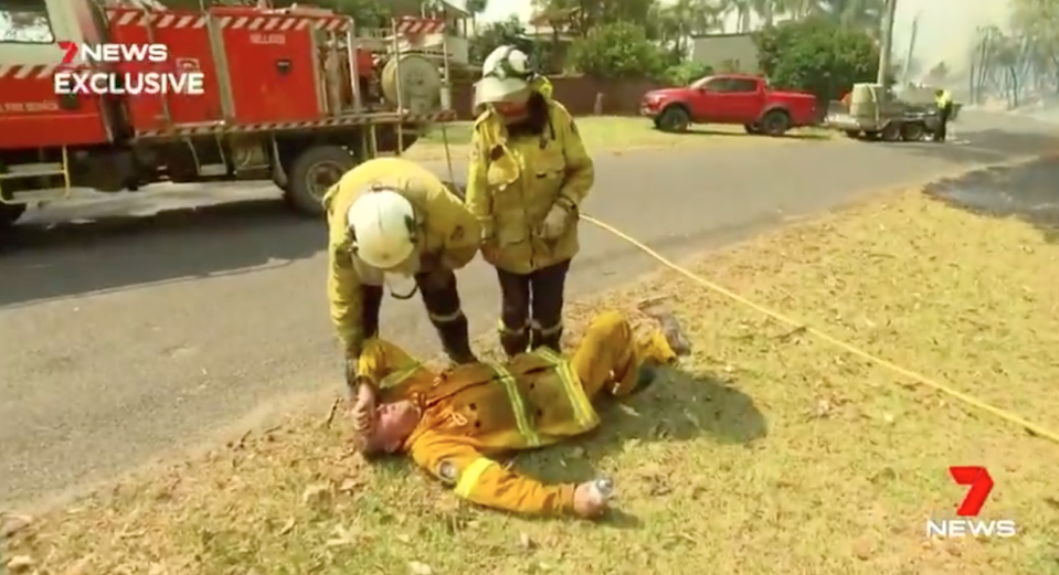 Paul Parker collapses on the ground as he battles NSW fires.