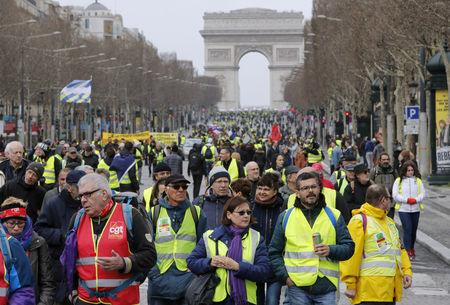 "FILE PHOTO: Protesters wearing yellow vests walk down the Champs Elysees during a demonstration by the ""yellow vests"" movement in Paris"