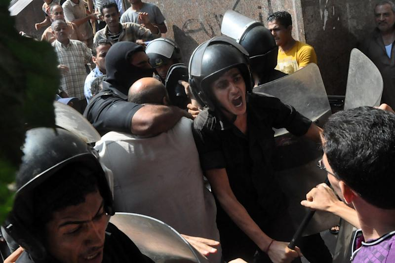 Egyptians security forces escort an Islamist supporter of the Muslim Brotherhood out of the al-Fatah mosque and through angry crowds, after hundreds of Islamist protesters barricaded themselves inside the mosque overnight, following a day of fierce street battles that left scores of people dead, near Ramses Square in downtown Cairo, Saturday, Aug. 17, 2013. (AP Photo/Hussein Tallal)