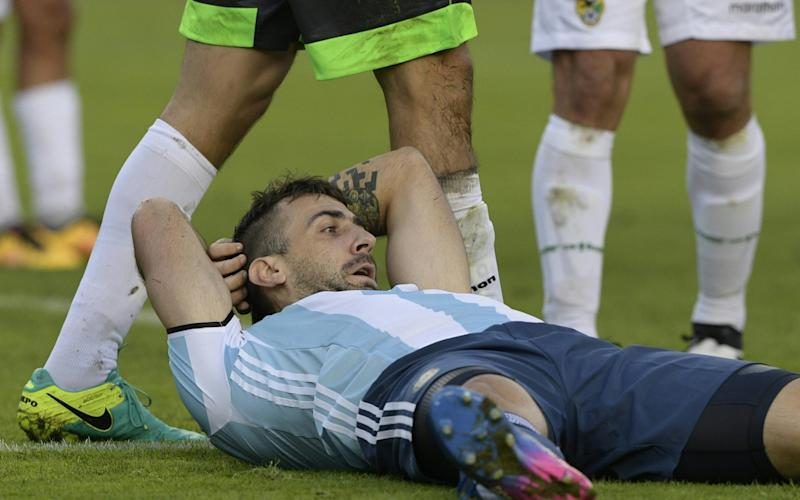 Argentina's forward Lucas Pratto lays on the field after his team loses against Bolivia - Credit: AFP