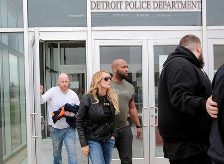 Adult film star Stormy Daniels, whose real name is Stephanie Clifford, and her security leave the Detroit Police Department 4th Precinct after picking up her temporary Dance Permit license to perform at a club in Detroit, Michigan, U.S., April 18, 2018.  REUTERS/Rebecca Cook