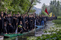 Kashmiri Shiite Muslims shout religious slogans as they participate in a Muharram procession on wooden boats in the interiors of Dal lake, outskirts of Srinagar, Indian-controlled Kashmir, Wednesday, Aug. 18, 2021. Muharram is a month of mourning in remembrance of the martyrdom of Imam Hussein, the grandson of Prophet Mohammed. (AP Photo/ Dar Yasin)