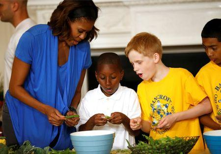 U.S. first lady Obama helps prepare a salad using the summer crop from the White House Kitchen Garden at the White House in Washington