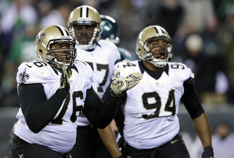 New Orleans Saints' Akiem Hicks (76) and Cameron Jordan (94) celebrate after tackling Philadelphia Eagles' Nick Foles during the second half of an NFL wild-card playoff football game, Saturday, Jan. 4, 2014, in Philadelphia. (AP Photo/Michael Perez)
