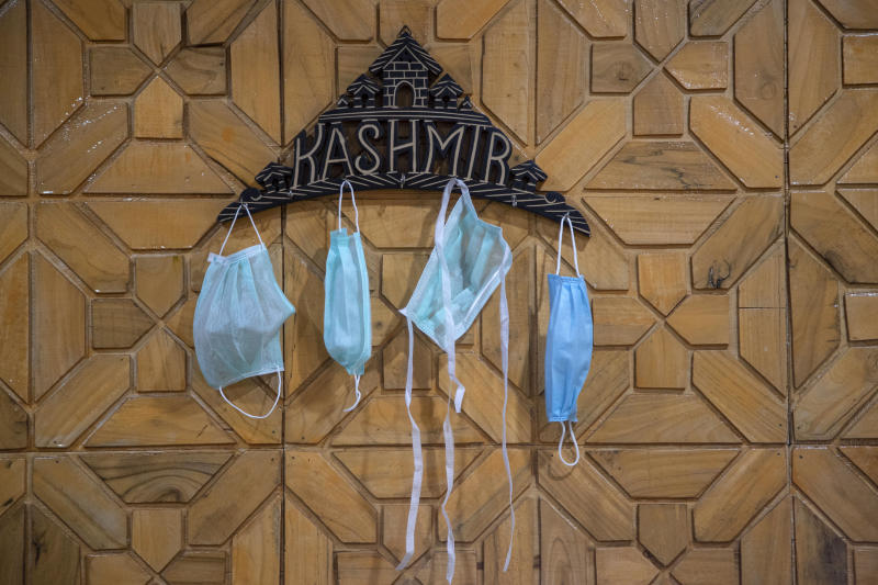Surgical masks hang on a key holder inside a residential house in Srinagar, India, Saturday, June 13, 2020. Markets, including non-essential business establishments, opened in the Indian portion of Kashmir on Saturday after more than two and a half months of lockdown to control the spread of the coronavirus. However, only 50 percent shops will be allowed to run on alternate days in the valley. (AP Photo/Mukhtar Khan)