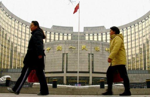 Pedestrians walk past the People's Bank of China in Beijing. China's move to allow more competition in its state-dominated banking sector revives a reform shelved for nearly a decade and defies expectations of a policy freeze before leadership change this year