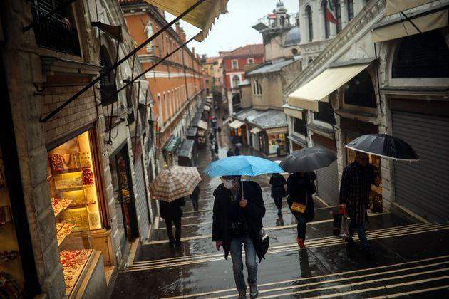 People shelter against the rain with umbrellas as they walk along the Rialto bridge on a rainy day in Venice, Sunday, March 1, 2020. In northern Italy, the virus COVID-19 is taking a deep social toll, curtailing the usual opportunities to meet. (AP Photo/Francisco Seco) (Photo: via Associated Press)