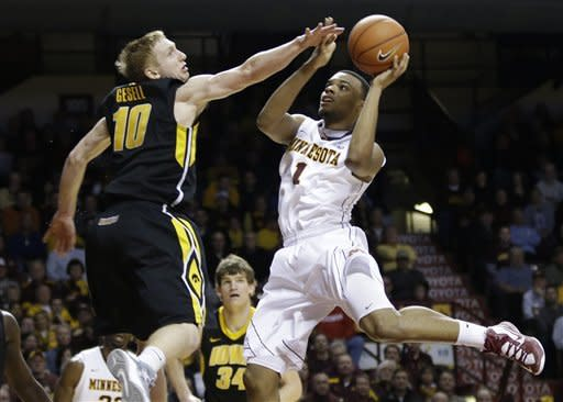 Minnesota's Andre Hollins, right, lays up as Iowa's Mike Gesell tries to block the shot in the second half of an NCAA college basketball game on Sunday, Feb. 3, 2013, in Minneapolis. Minnesota won 62-59. (AP Photo/Jim Mone)