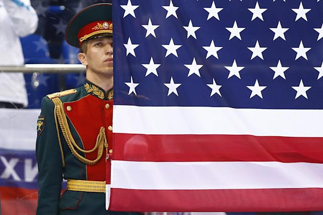 A Russian honor guard soldier stands behind the United States flag after the gold medal ice sledge hockey match between United States and Russia at the 2014 Winter Paralympics in Sochi, Russia, Saturday, March 15, 2014. United States won 1-0. (AP Photo/Pavel Golovkin)