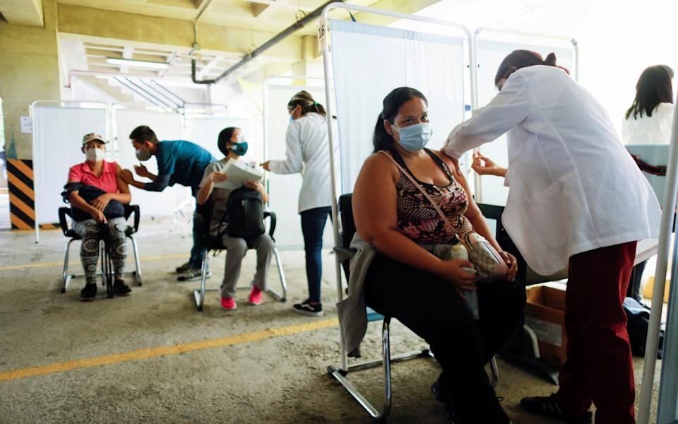 People receive their first dose of Russia's Sputnik V vaccine against the coronavirus disease (COVID-19), in the parking lot of the Social Security Institute of the Armed Forces, turned into a mass vaccination centre, in Caracas - Reuters