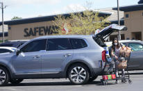 In this Wednesday, May 19, 2021, photograph, a shopper wearing a face mask loads her purchases into a sports-utility vehicle outside a Safeway grocery store in Aurora, Colo. Many workers in retail sales jobs who are fully vaccinated are concerned about risks posed as retailers change their mask-wearing policies for customers. (AP Photo/David Zalubowski)
