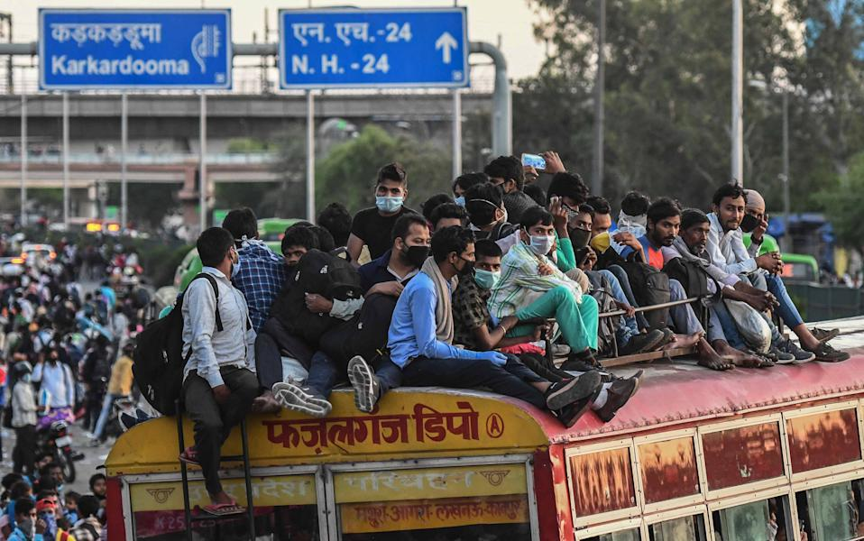 NEW DELHI, INDIA - MARCH 28: A huge rush of migrant workers who had been marching to their homes, seen at Anand Vihar Bus Terminal on day 4 of the nationwide lockdown to check the spread of coronavirus, on March 28, 2020 in New Delhi, India. (Photo by Biplov Bhuyan/Hindustan Times via Getty Images)