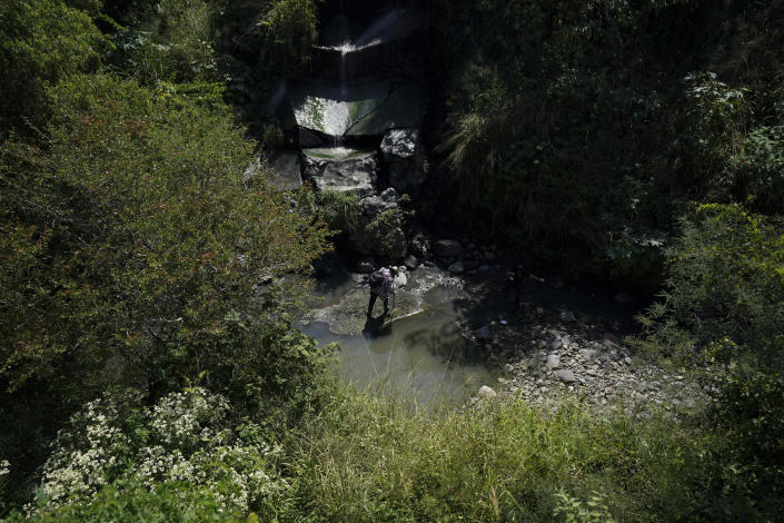 A volunteer inspects an area suspected of hiding the bodies of some missing people on the outskirts of Cuautla, Mexico, Tuesday, Oct. 12, 2021. The government's registry of Mexico's missing has grown more than 20% in the past year and now approaches 100,000. (AP Photo/Fernando Llano)