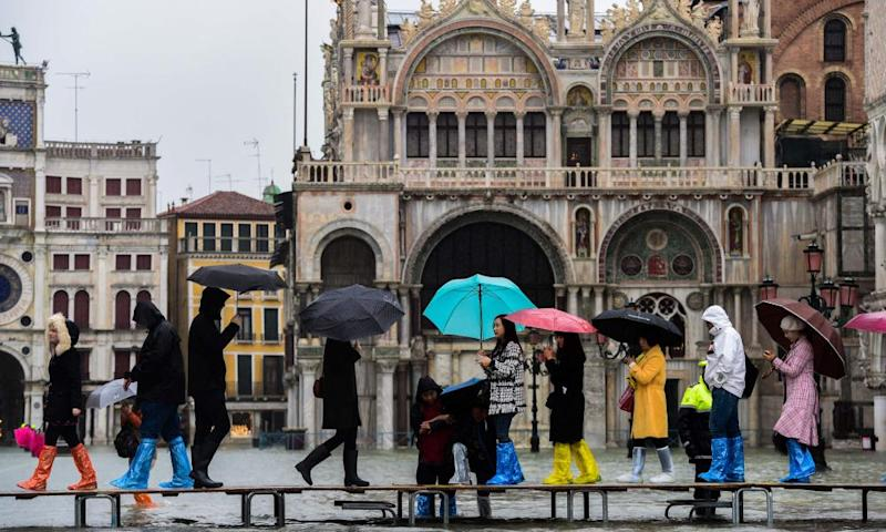 Tourists walk across a footbridge on the flooded St Mark's Square in Venice.