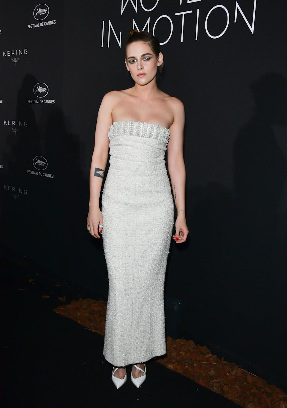 <p>Kristen Stewart was clad in yet another Chanel number for the Kering Women In Motion dinner. This time it was a tweet, white column dress with embellishment, which she wore with white pumps. [Photo: Getty] </p>