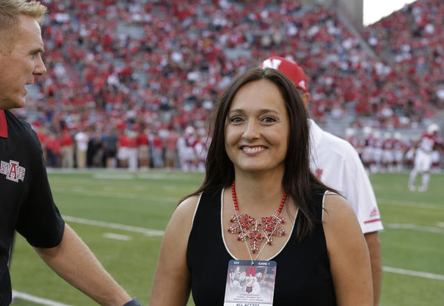 "FILE - In this Sept. 2, 2017, file photo, Wendy Anderson, center, wife of Arkansas State head coach Blake Anderson, obscured at left, smiles after chatting with Nebraska head coach Mike Riley, rear, before an NCAA college football game in Lincoln, Neb. Wendy Anderson has died after a two-year fight with breast cancer. Blake Anderson says his wife died Monday night, Aug. 19, 2019, just hours after the school announced he would be taking a leave of absence. He said on Twitter : ""She passed as peacefully & gracefully as you could ever hope."" (AP Photo/Nati Harnik, File)"