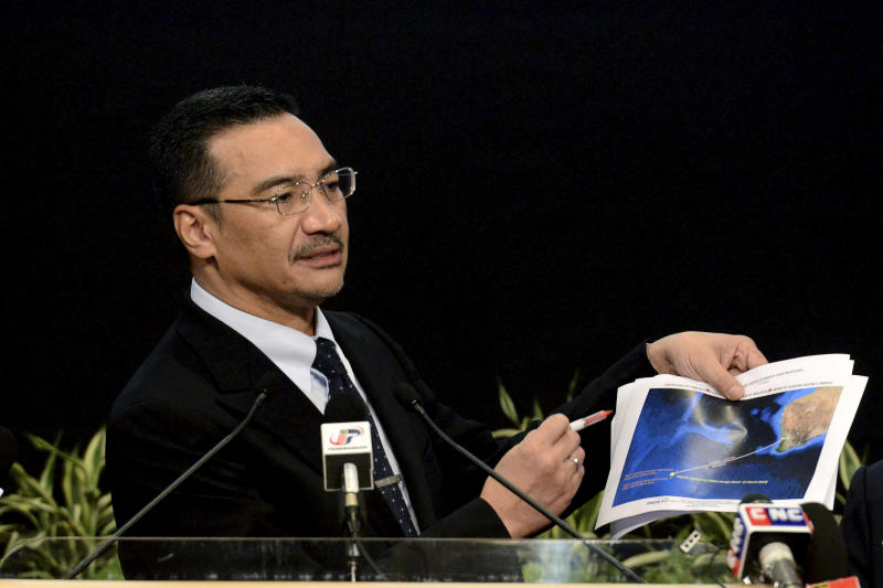 """FILE - In this Wednesday, March 26, 2014 file photo, Malaysia's Defense Minister and acting Transport Minister Hishammuddin Hussein shows a printout of the latest satellite image of objects that might be from the missing Malaysia Airlines plane, at Putra World Trade Center in Kuala Lumpur, Malaysia. Hussein has been pressed on whether there might be any survivors. He has said he was still """"hoping against hope"""" that passengers might be still found alive. This response was seen by some as contradictory to the Malaysian Airlines statement, creating a new discrepancy even on something which is fundamentally unknowable. (AP Photo/Joshua Paul, File)"""