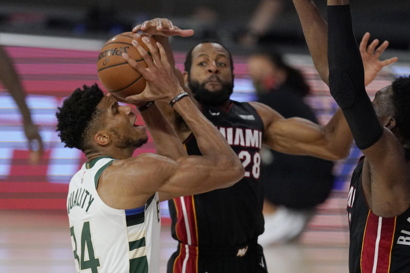 Milwaukee Bucks' Giannis Antetokounmpo (34) goes to the basket defended by Miami Heat's Andre Iguodala (28) in the second half of an NBA conference semifinal playoff basketball game Friday, Sept. 4, 2020, in Lake Buena Vista, Fla. (AP Photo/Mark J. Terrill)