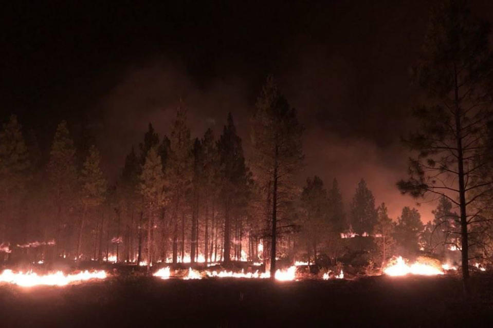 In this photo provided by the Bootleg Fire Incident Command, the Bootleg Fire burns at night near Highway 34 in southern Oregon on Thursday, July 15, 2021. Firefighters scrambled Friday to control a raging inferno in southeastern Oregon that's spreading miles a day in windy conditions, one of numerous wildfires across the U.S. West that are straining resources. The Bootleg Fire, the largest wildfire burning in the U.S., has torched more than 377 square miles (976 square kilometers), and crews had little control of it. (Jason Pettigrew/Bootleg Fire Incident Command via AP)