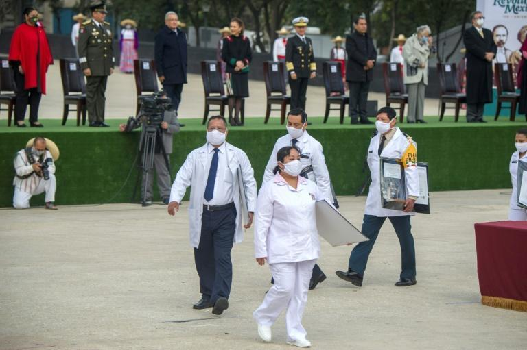 Medical personnel receive decorations during the commemoration of the 110th anniversary of the Mexican Revolution at the Monument to the Revolution in Mexico City