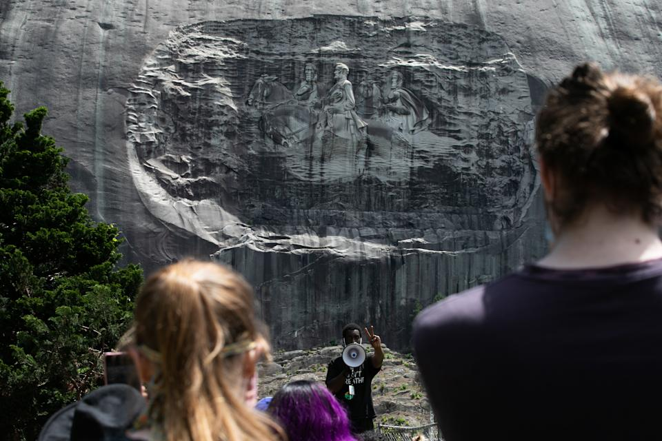 STONE MOUNTAIN, GA - JUNE 16: Organizer Quintavious Rhodes addresses Black Lives Matter protesters during a march in Stone Mountain Park to the Confederate carving etched into the stone side of the mountain on June 16, 2020 in Stone Mountain, Georgia. The march is to protest confederate monuments and recent police shootings.  Stone Mountain Park features a Confederate Memorial carving depicting Stonewall Jackson and Robert E. Lee, President Jefferson Davis.  (Photo by Jessica McGowan/Getty Images)