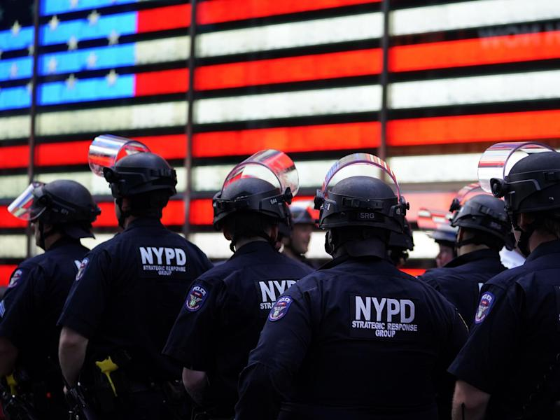 NYPD police officers watch demonstrators in Times Square on 1 June, 2020, during a Black Lives Matter protest: (AFP)