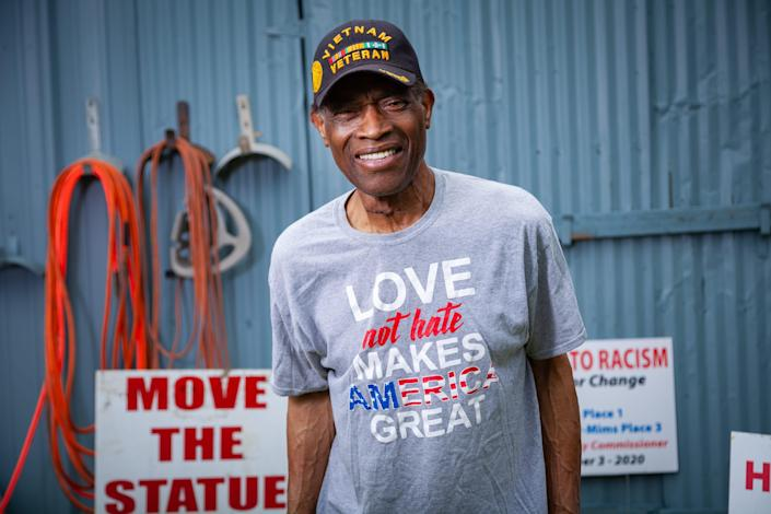 """A man stands in front of a shed surrounded by signs like """"Move the Statue"""""""
