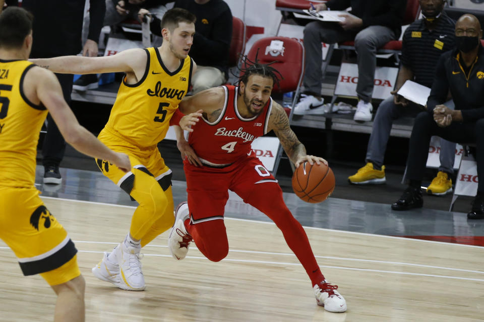 Ohio State's Duane Washington, right, drives the baseline against Iowa's C.J. Fredrick during the first half of an NCAA college basketball game Sunday, Feb. 28, 2021, in Columbus, Ohio. (AP Photo/Jay LaPrete)