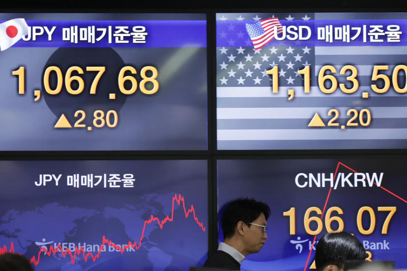 A currency trader walks past in front of the screens showing the foreign exchange rates at the foreign exchange dealing room in Seoul, South Korea, Wednesday, Nov. 13, 2019. Asian stocks sank Wednesday after U.S. President Donald Trump threatened more tariff hikes on Chinese imports if talks aimed at ending a trade war fail to produce an interim agreement. (AP Photo/Lee Jin-man)
