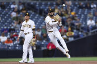 San Diego Padres shortstop Fernando Tatis Jr. throws to first base after fielding a grounder by New York Mets' Kevin Pillar as Manny Machado, left, looks on in the second inning of a baseball game Saturday, June 5, 2021, in San Diego. Pillar was out at first. (AP Photo/Derrick Tuskan)