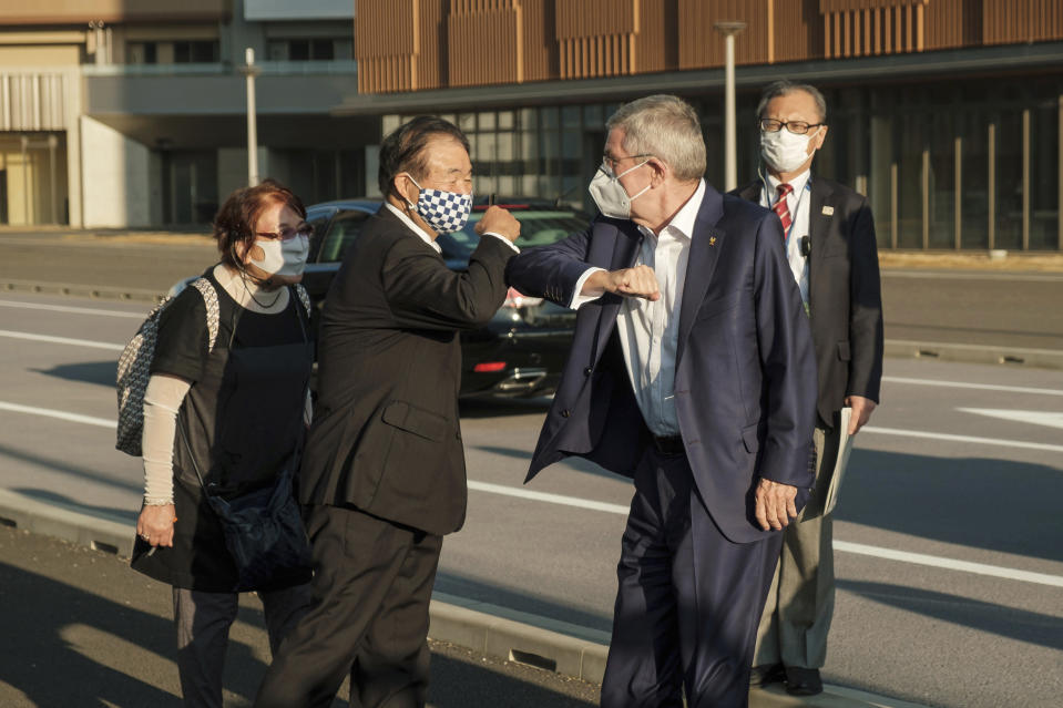 "IOC President Thomas Bach, right in foreground, wearing a protective mask greets Tokyo 2020 Vice President Endo Toshiaki during a visit to Olympic and Paralympic Village in Tokyo Tuesday, Nov. 17, 2020. Bach said during this week's trip to Tokyo that he is ""encouraging"" all Olympic ""participants"" and fans to be vaccinated - if one becomes available - if they are going to attend next year's Tokyo Olympics. (Nicolas Datiche/Pool Photo via AP)"
