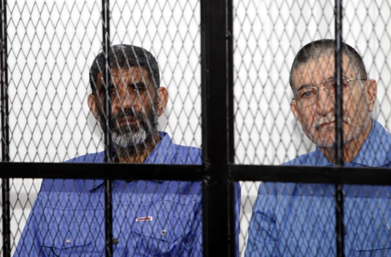 Abdullah al-Senussi and Bouzaid Dorda sit behind bars during a hearing at a courtroom in Tripoli