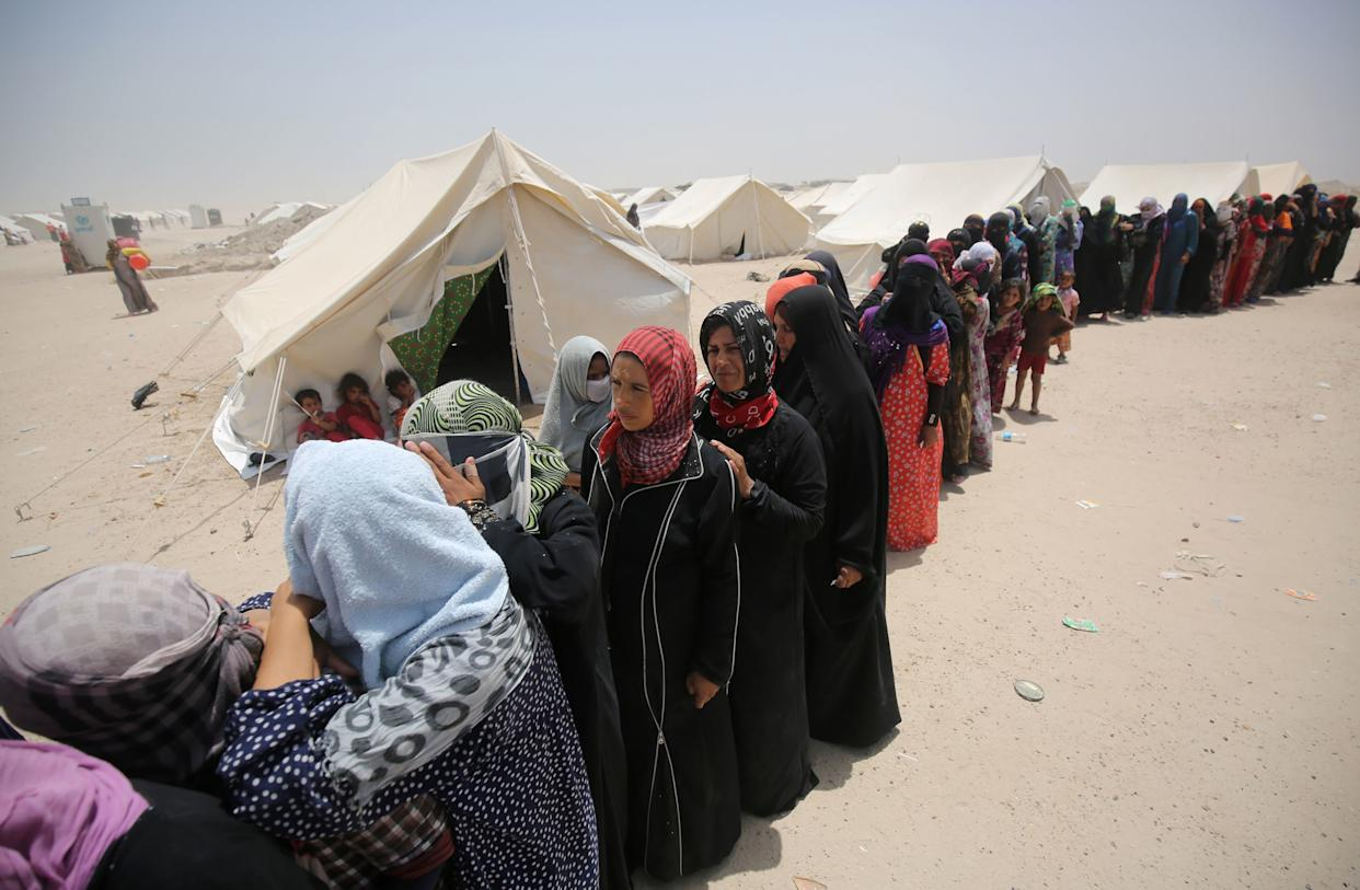 Iraqis women displaced from the city of Fallujah queue up to collect aid distributed by the Norwegian Refugee Council at a newly opened camp where they are taking shelter in Amriyat al-Fallujah on June 27, 2016, south of Fallujah.