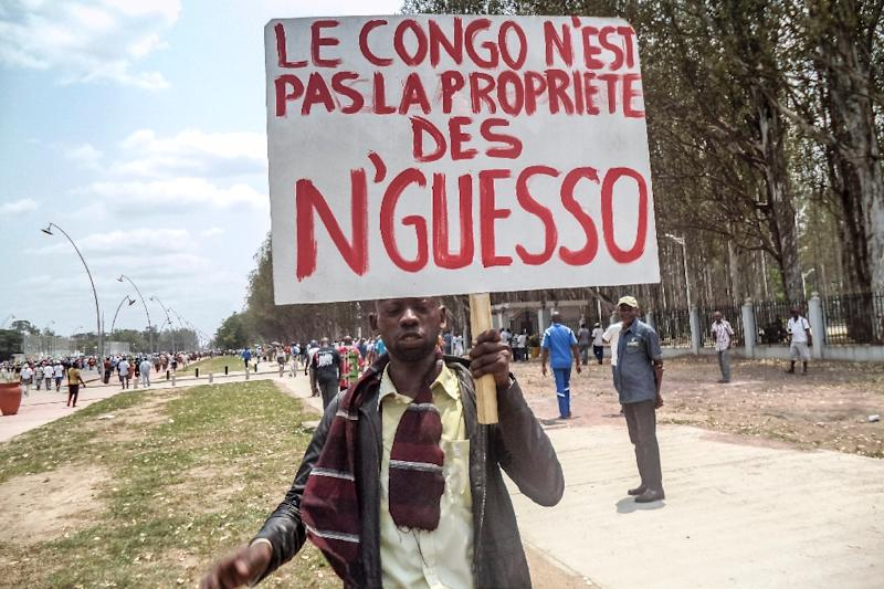 """A man holds a placard reading """"Congo is not the property of N'Guesso"""" during an opposition demonstration in Brazzaville on September 27, 2015. Thousands of people staged a mass demonstration in Congo's capital Brazzaville to protest plans by veteran ruler Denis Sassou Nguesso to try to extend his rule. AFP PHOTO / LAUDES MARTIAL MBON (AFP Photo/Laudes Martial Mbon)"""