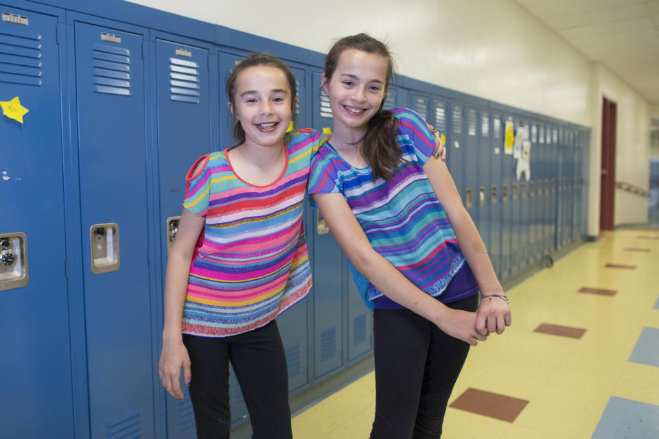 In this Thursday, June 6, 2013 photo, Katie Thomas, left, and her twin sister, Megan, one of the twenty-four sets of twins from Highcrest Middle School in Wilmette, Ill., pose for a portrait at the school. The group is attempting to break a Guinness World record for the amount of twins in one grade which is currently sixteen sets. (AP Photo/Scott Eisen)