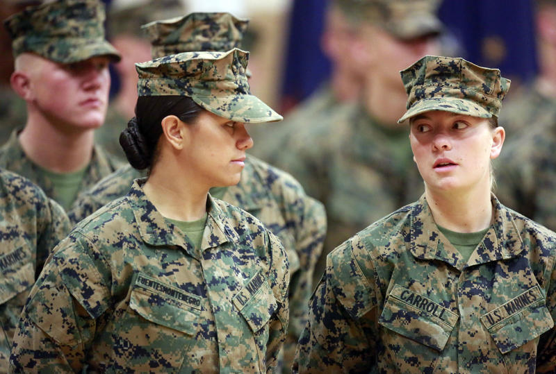 Private First Class Cristina Fuentes Montenegro, 25, left, shares a moment with Pfc. Julia Carroll, 18, during graduation ceremony held on Camp Geiger, Jacksonville, Thursday, Nov. 21, 2013. Montenegro and Carroll were two of the three female Marines who became the first women to graduate from the Corps' tough-as-nails enlisted infantry training school in North Carolina. The three completed the rigorous 59-day course and met the same test standards as the men, said Marine Corps spokeswoman Capt. Geraldine Carey. (AP Photo/The Daily News, John Althouse)