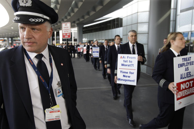 "FILE- In this Thursday, Sept. 20, 2012, file photo, Captain Mike McClellan, ORD Domicile Chairman of the Allied Pilots Association left, joins over 200 American Airline pilots marching on a picket line at O'Hare International Airport, in Chicago.  American Airlines said Thursday, Sept. 27, 2012,  if pilots don't end actions that are disrupting its flights, it will take their union to court. A top American Airlines executive told union leaders that some pilots were conducting ""an unlawful, concerted effort to damage the company"" by filing more maintenance complaints and other tactics, leading to a surge in late and canceled flights.(AP Photo/M. Spencer Green, File)"