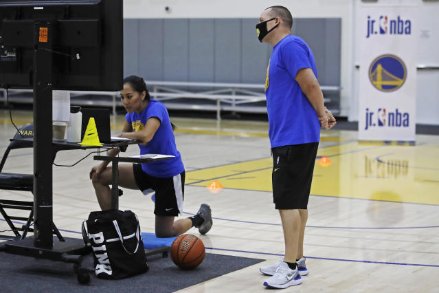 In this photo taken on Tuesday, June 9, 2020, Golden State Warriors basketball camp director Jeff Addiego, right, supervises coach Chanel Antonio as she speaks with her virtual students in Oakland, Calif. The Warriors had to adapt their popular youth basketball camps and make them virtual given the COVID-19 pandemic. (AP Photo/Ben Margot)