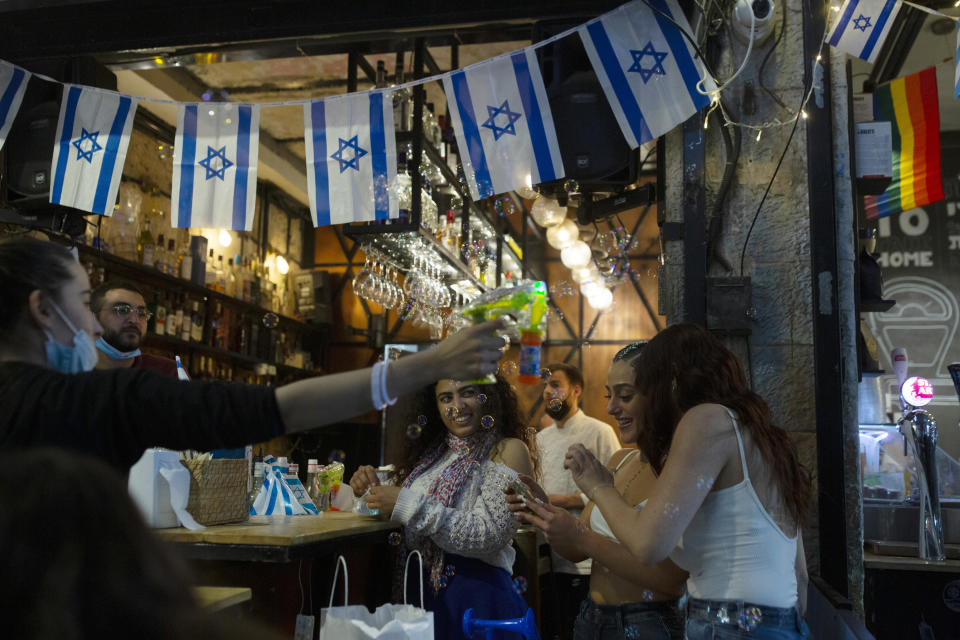 Israeli women check a selfie they took at a bar as they celebrate Independence Day at the Mahane Yehuda Market in Jerusalem, after more than a year of coronavirus restrictions, Wednesday, April 14, 2021. (AP Photo/Maya Alleruzzo)
