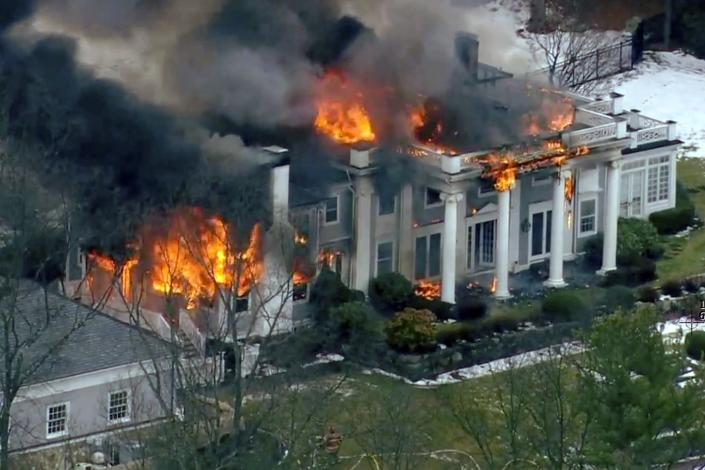 This aerial still image from video provided by WCVB shows a mansion ablaze Friday, Dec. 27, 2019, in Concord, Mass. Firefighters are battling a blaze at the mansion in the Boston suburbs, as flames can be seen shooting out of the roof of the 6,500-square-foot home. (WCVB-TV via AP)