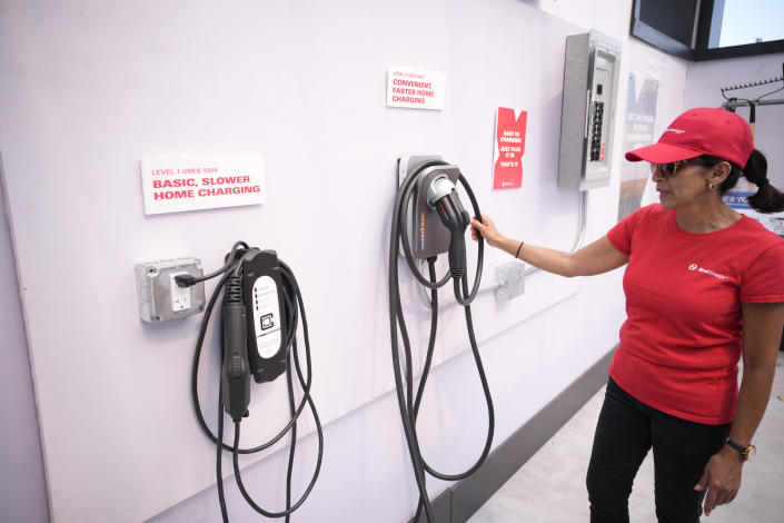 An Xcel Energy representative checks over chargers for EVs on display in the Xcel exhibit at the Denver auto show Friday, Sept. 17, 2021 in Colorado. (AP Photo/David Zalubowski)