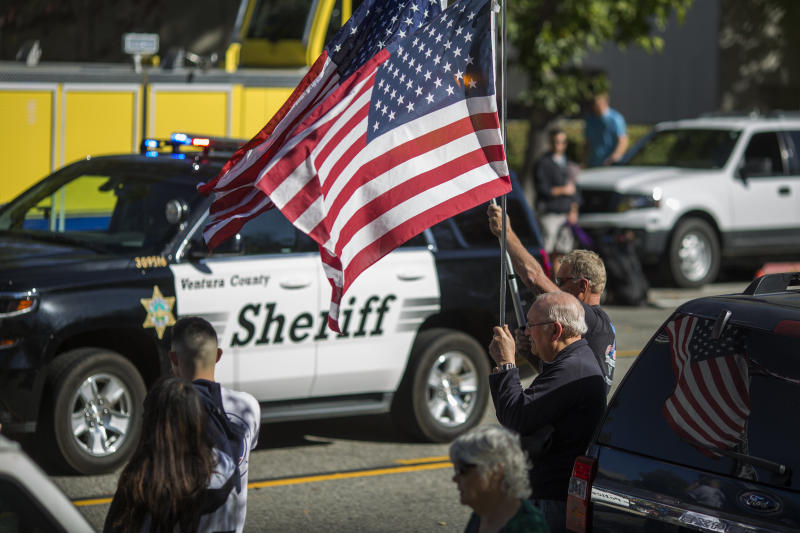 A man waves a flag in Thousand Oaks, California, as a Ventura County Sheriff's patrol car passes. Deputies visited the suspected gunman's home in April.