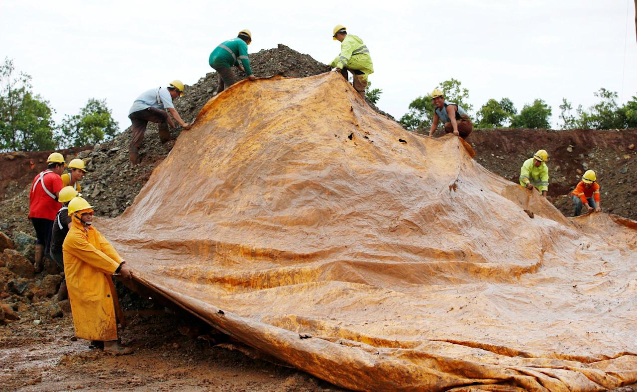 Workers of SR Metals cover a stockpile of nickel-ore minerals with a tarp to avoid moisture in Tubay, Agusan del Sur, in southern Philippines February 16, 2017. Picture taken February 16, 2017.    REUTERS/Erik De Castro