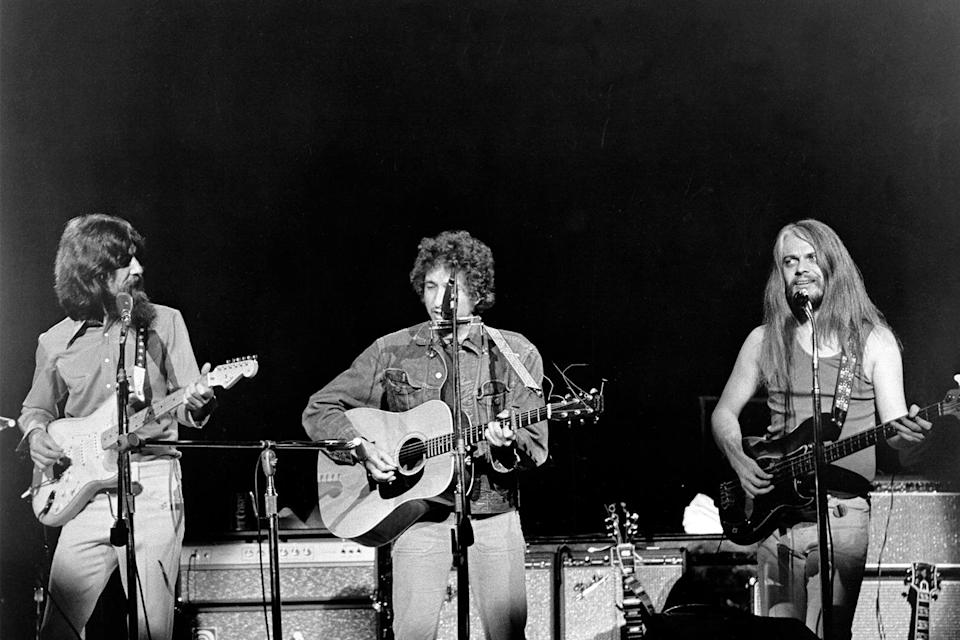 George Harrison, Bob Dylan and Leon Russell perform onstage