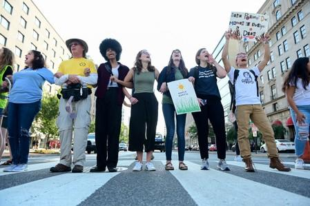 Climate change activists block traffic at an intersection near the White House in Washington
