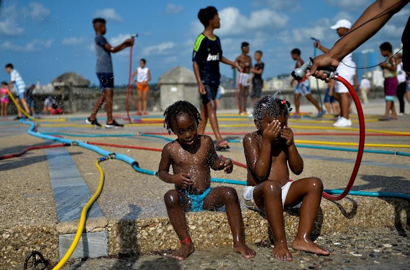 Children play with hoses as part of an art installation during the 13th Havana Biennial (AFP Photo/Yamil LAGE)