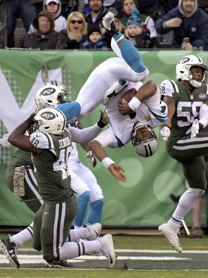 <p>Carolina Panthers quarterback Cam Newton (1) dives over the tackle attempt of New York Jets outside linebacker Jordan Jenkins (48) on a two-point conversion score during the second half of an NFL football game, Sunday, Nov. 26, 2017, in East Rutherford, N.J. (AP Photo/Bill Kostroun) </p>