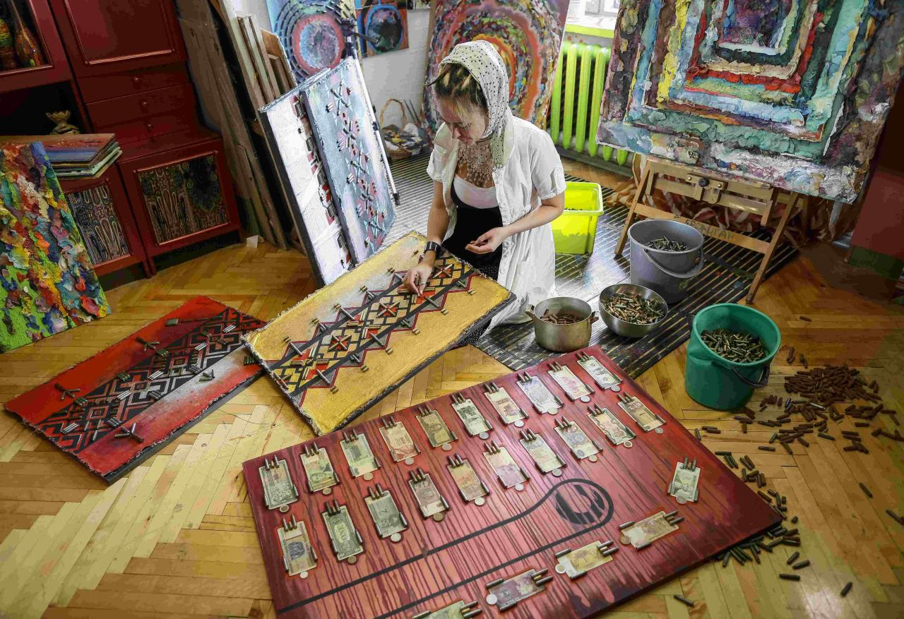 Ukrainian artist Dariya Marchenko works in her studio at pictures which consist of cartridges brought from the frontline in eastern Ukraine, in Kiev, July 22, 2015. Daria Marchenko calls her art approach philosophic symbolism where every element has its hidden meaning. In her works cartridges mean human's life that was brutally ended. Picture taken July 22, 2015. REUTERS/Gleb Garanich